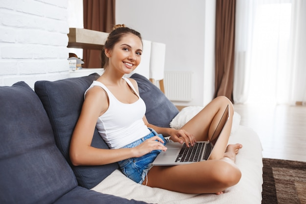 Ragazza sorridente attraente che si siede nel salone e che tiene computer portatile.