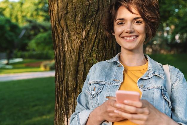 Привлекательная улыбающаяся молодая девушка в повседневной одежде проводит время на открытом воздухе в парке, опираясь на дерево, используя мобильный телефон