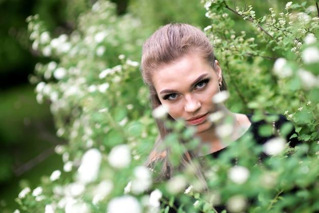 하얀 꽃이 만발한 덤불의 배경에 대해 야외에서 검은색 스웨터를 입고 부드러움과 부드러움을 입은 매력적인 웃는 어린 소녀