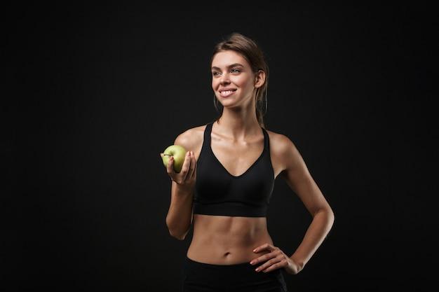 녹색 사과 들고 검은 배경 위에 절연 스포츠 브래지어와 반바지를 입고 매력적인 웃는 젊은 건강 피트니스 여자