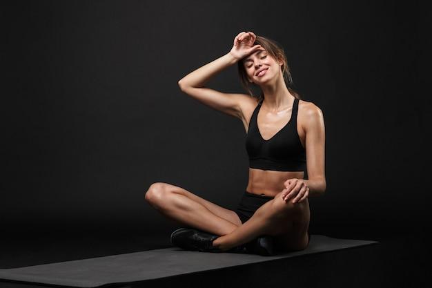 Привлекательная улыбающаяся молодая здоровая фитнес-женщина в спортивном бюстгальтере и шортах, изолированных на черном фоне, отдыхает после тренировки на фитнес-коврике