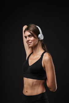 Attractive smiling young healthy fitness woman wearing sports bra and shorts isolated over black background, listening to music with headphones