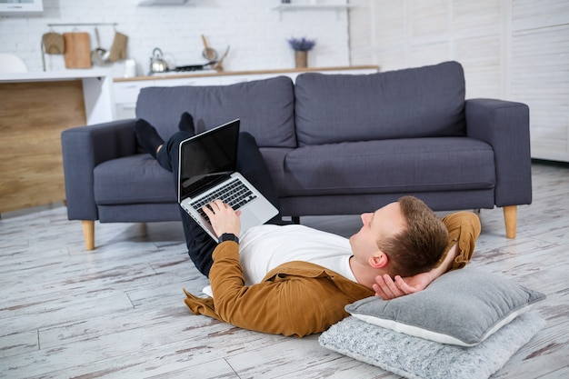 Attractive smiling young man in casual wear sitting on floor on sofa in living room using laptop computer
