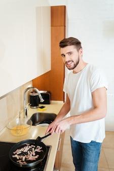 魅力的な笑顔の若い男料理と揚げ物がキッチンで出会う