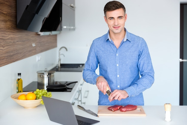 自宅の台所で肉を調理する青いたわごとの魅力的な笑顔の若い男