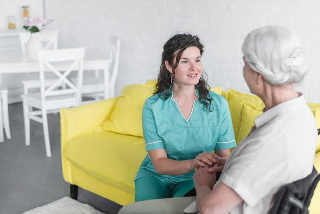 An attractive smiling young woman giving support to senior woman patient