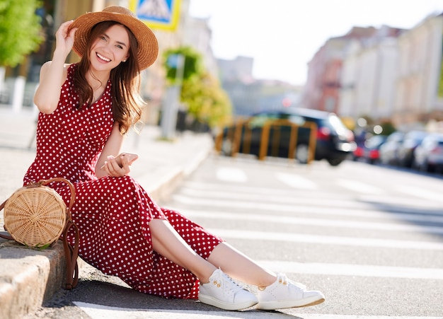 캐주얼 옷에 매력적인 웃는 젊은 여자는 야외에서 휴대 전화를 사용