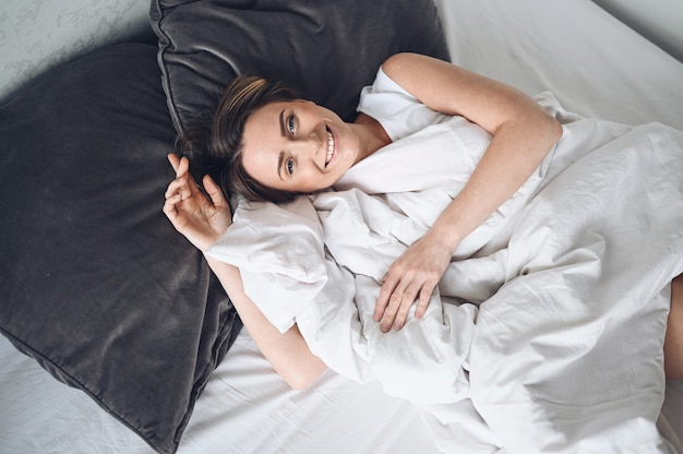 Привлекательная улыбающаяся молодая женщина, растягивающаяся в постели, просыпающаяся одна счастливая концепция, бодрствующая после здорового сна в удобной удобной кровати, и матрас наслаждаются добрым утром