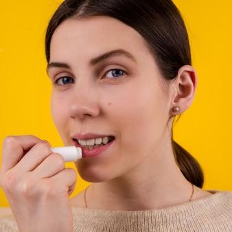 노란색 바탕에 위생 립스틱을 사용 하여 매력적인 웃는 젊은 여자. 입술 관리 및 보호.