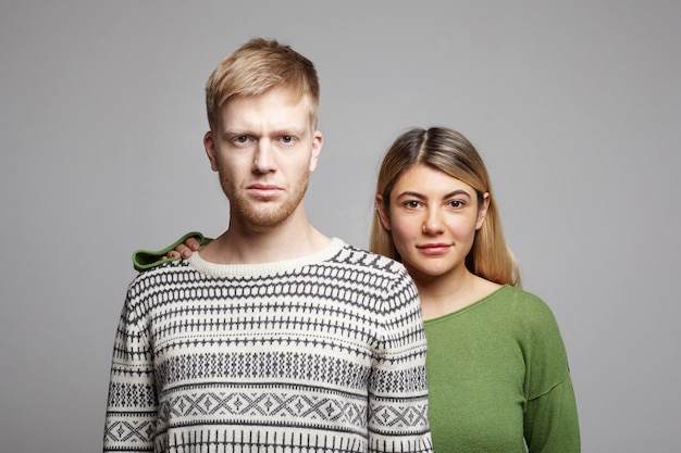 Attractive smiling young woman with blonde hair standing behind serious unshaven man, holding hand on his shoulder as sign of support, standing at grey wall with copy space for your information