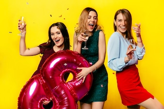 Attractive smiling young women with wineglasses of champagne