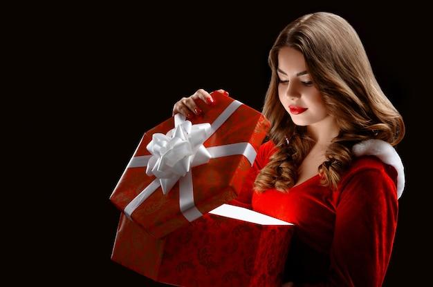 Привлекательная снегурочка открывает большой красный подарок на новый год