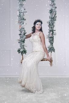 Attraente regina delle nevi su altalena