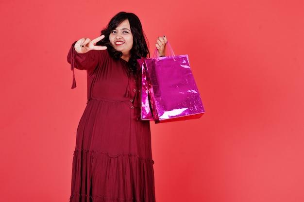 Привлекательная южно-азиатская женщина в темно-красном платье позирует на розовой стене с яркими цветными сумками.