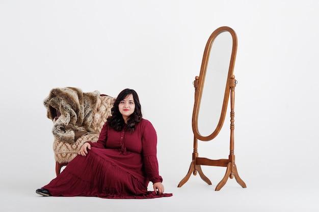 Привлекательная южно-азиатская женщина в темно-красном платье позирует на белой стене против зеркала и стула.