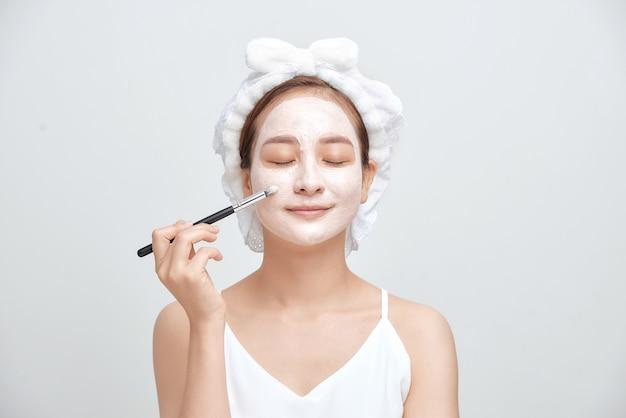 白い背景で隔離の顔の粘土マスクを適用する魅力的なスパの女性。