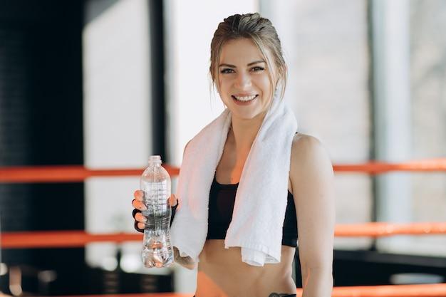 魅力的なスポーツ少女の笑みを浮かべて、フィットネスクラスに立っている間水を飲む