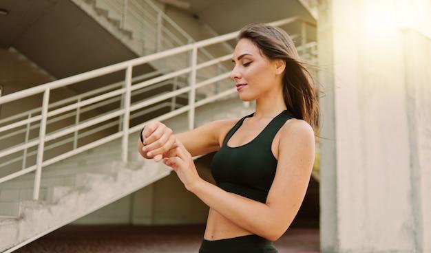 スポーツウェアの魅力的なスポーツ女性は、都市環境で屋外でスマートウォッチを使用します