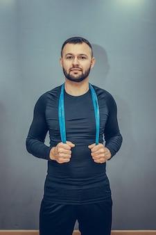 Привлекательный спортивный мужчина в стильной спортивной одежде, протягивая руки с резинкой во время тренировки на серой стене.