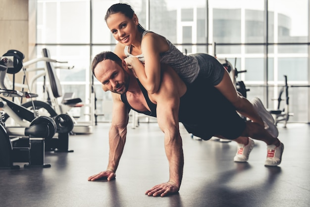 Attractive sports people are working out together in gym.