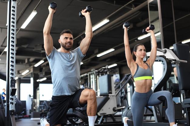 魅力的なスポーツの人々はジムでダンベルを使って運動しています。