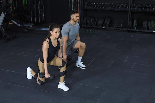 Привлекательные спортсмены занимаются с гантелями в тренажерном зале.