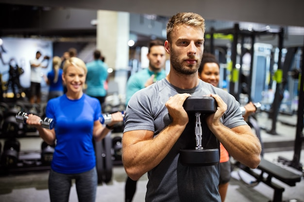 매력적인 스포츠 사람들 친구들이 체육관에서 운동하고 있습니다