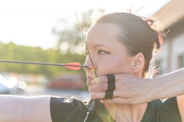 アーチェリー、矢印、弓のアクションで魅力的なスポーツの女性