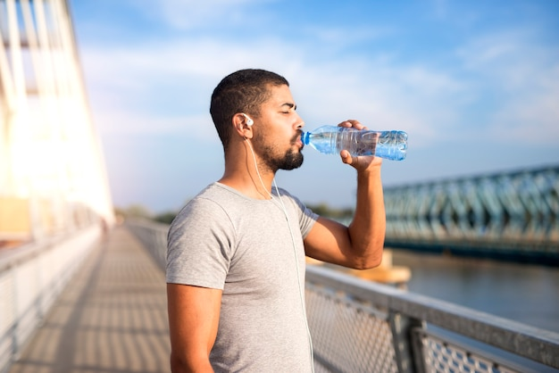 Attractive sportsman drinking water after hard training