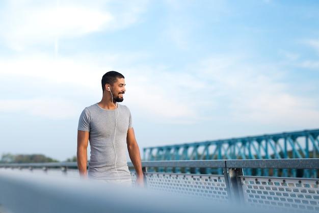 Привлекательный спортсмен улыбается и смотрит в сторону, готовится к бегу