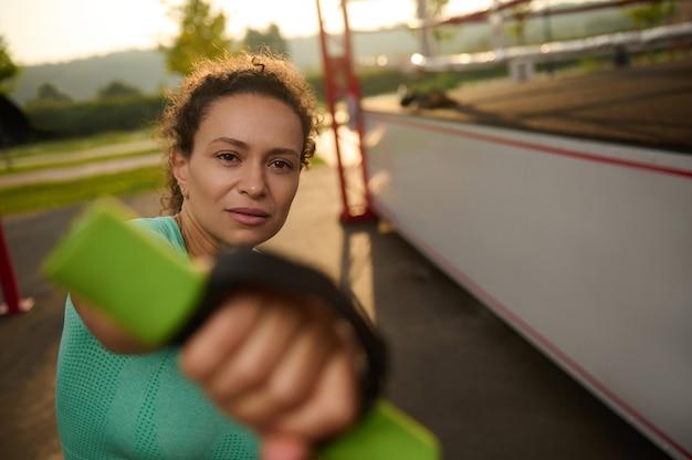 이른 아침에 운동하는 매력적인 운동가, 운동장에서 복싱을 위해 아령을 사용하여 심장 강화 훈련을 하고 있습니다.