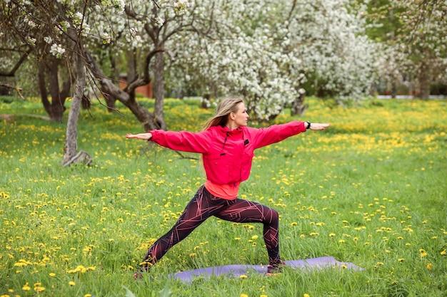 Привлекательная спортсменка занимается йогой на открытом воздухе в цветущем парке весной