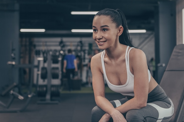 Attractive sportswoman smiling cheerfully, looking away, relaxing at the gym