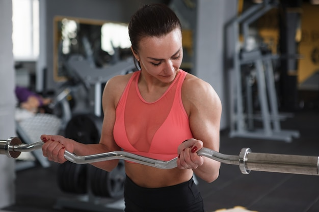 Attractive sportswoman working out with barbell at the gym