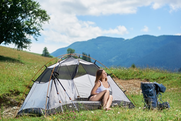 Attractive sporty female traveller sitting in tent beside backpack and trekking sticks, smiling, looking away, resting after hiking, enjoying summer day in the mountains.