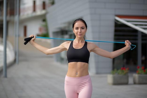 縄跳びで手のトレーニングをしている魅力的なスポーティな女の子