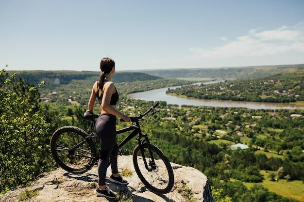 川、町、青い空を背景に山の岩の上に立っている魅力的なスポーティな女の子