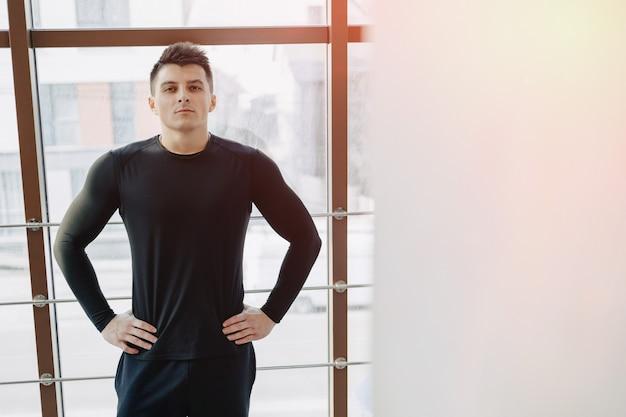 Привлекательный спортивный парень у окна. спортсмен позирует возле просторных окон. тренажерный зал и спорт.