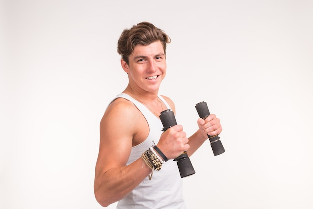 An attractive sporty man shows his biceps and smiling on white background