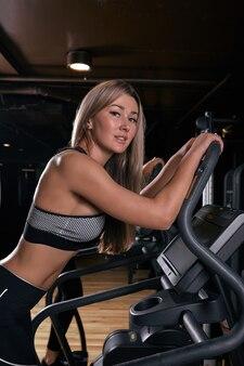 Привлекательная спортивная женщина на велотренажерах во время тренировки на велосипеде в тренажерном зале