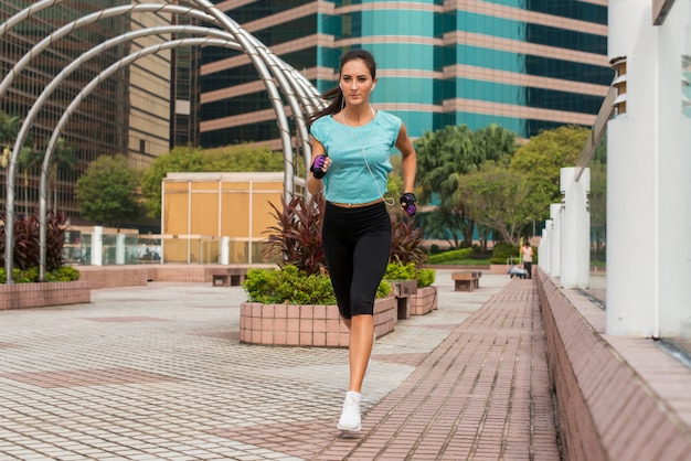 Attractive sporty young woman running on pavement