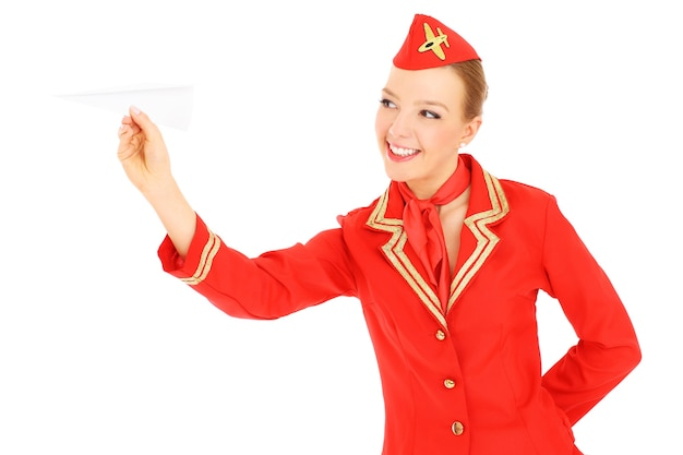 An attractive stewardess playinh with a paper plane over white background