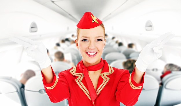 An attractive stewardess showing emergency exits in a plane