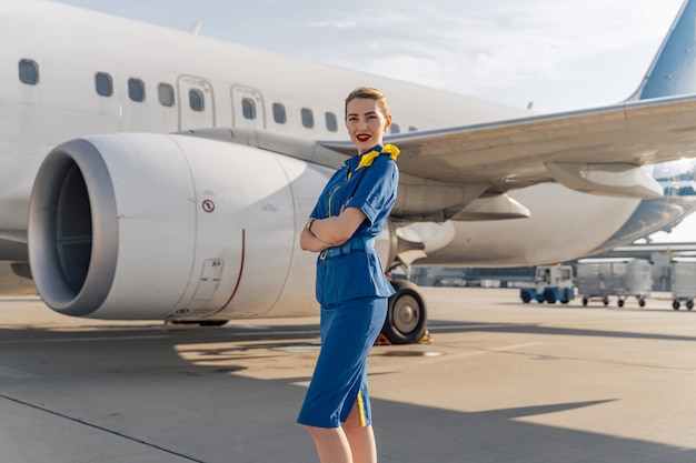 Привлекательная стюардесса стоит и позирует перед камерой