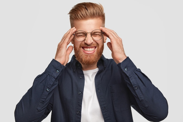 魅力的なストレスの多いセクシーな男性は歯を食いしばり、寺院に手を置き、頭痛があり、ファッショナブルな服を着て、白い壁に隔離されています。人、感情、感情