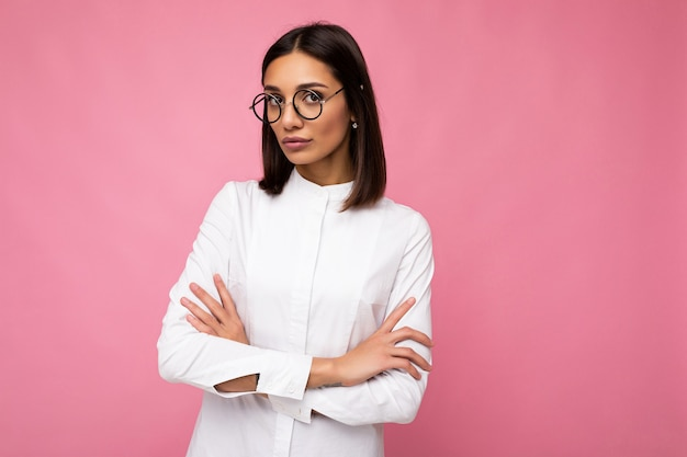 Attractive strict serious young brunette businesswoman wearing everyday stylish clothes and modern optical glasses isolated on colorful background wall looking at camera. copy space