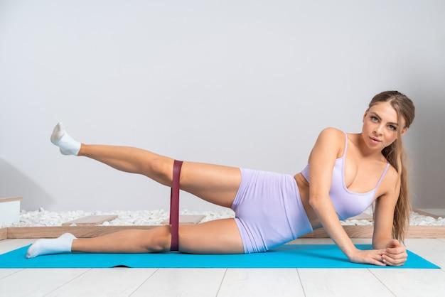Привлекательная сильная блондинка в розовой спортивной одежде делает упражнения на растяжку на полу с резинкой