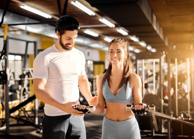Attractive strong muscular trainer showing biceps exercise with little dumbbells to an adorable smiling girl in the gym.