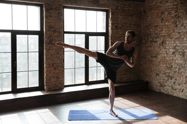 Lo sportivo forte attraente in palestra fa gli esercizi di yoga.