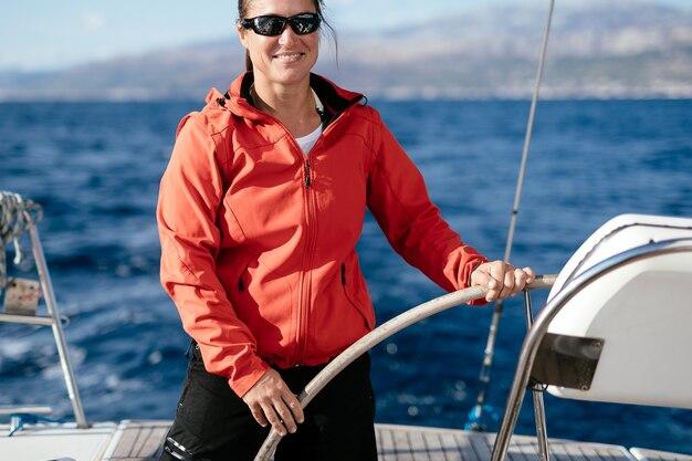 Привлекательная сильная женщина, плывущая со своей парусной лодкой